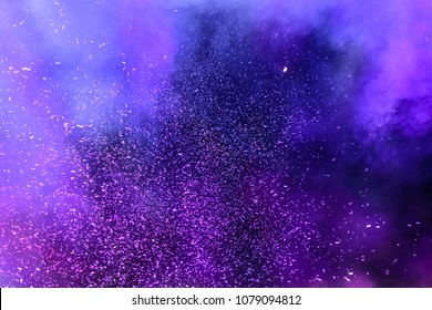 Confetti fired on air during a festival at night. Image ideal for backgrounds. Purple/magenta tonality. Smoke and lights in the middle of the multicolor confetti. Dark background as sky