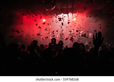 Confetti fired on air during a party in a disco. Confetti for background. Silhouette of happy people on dancefloor. Hands in the air