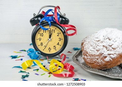 confetti and ribbon on retro clock with midnight time and New Years Dutch oliebollen on pewter plate