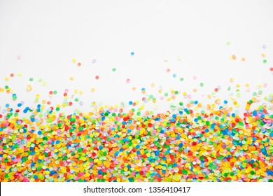 Confetti scattered in different colors on the white background. Festive confetti. The decor for the party.
