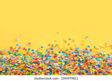 Confetti scattered in different colors on the yellow background. Festive confetti. The decor for the party.