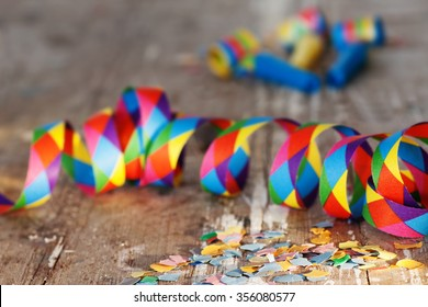 Confetti and streamers on rustic background