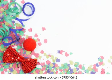 confetti, streamers and red bow on white background