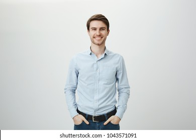 Confidence and business concept. Portrait of charming successful young entrepreneur in blue-collar shirt, smiling broadly with self-assured expression while holding hands in pockets over gray wall
