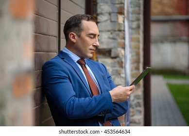 Confidence businessman having rest with technology