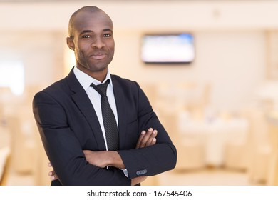 Confidence and charisma. Cheerful young African man in full suit keeping arms crossed and looking at camera