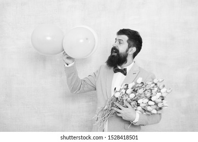 Confidence and charisma. Man bearded gentleman suit bow tie hold air balloons and bouquet. Gentleman making romantic surprise for her. Flowers delivery. Gentleman romantic date. Birthday greetings.