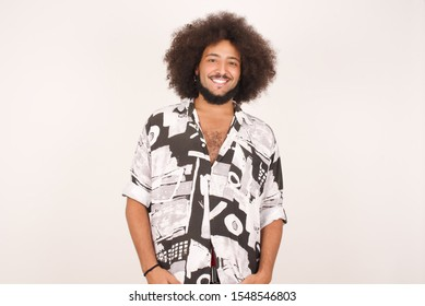 Confidence concept. Portrait of charming successful young African American man, smiling broadly with self-assured expression while holding hands in pockets standing against gray wall.