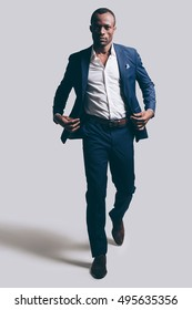 Confidence in every move. Full length of handsome young African man in full suit adjsuting his jacket while walking ahead and being in front of grey background