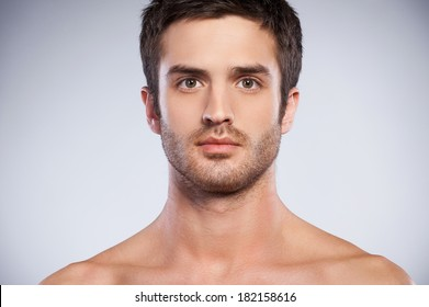 Confidence and masculinity. Portrait of handsome young beard man looking at camera while standing isolated on grey background