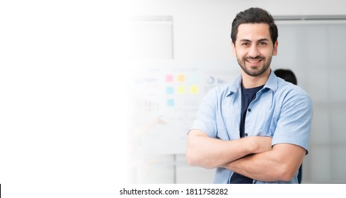 Confidence team leader. Young man owner startup business keeping arms crossed and looking at camera with smile while his colleagues working in the background