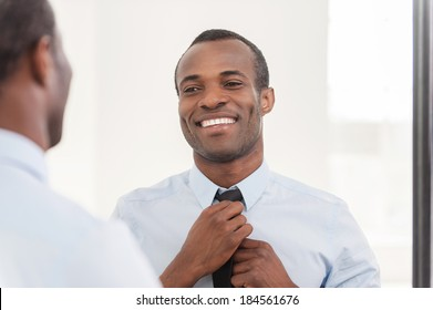 Confident about his look. Young African man adjusting his necktie while standing against mirror