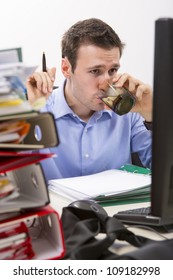 Confident accountant doing financial reports in front of his computer, drinking water, surrounded by huge piles of documents.