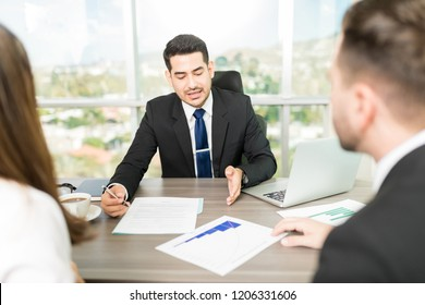 Confident accountant planning budget with colleagues at desk in office