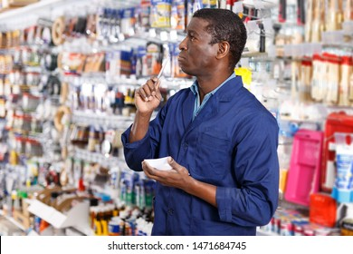 Confident adult African American worker taking inventory of goods in building materials store