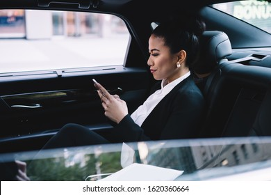 Confident adult Asian executive woman in formal clothes concentrating on screen and interacting with smartphone while sitting in luxurious automobile in city