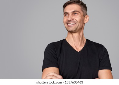 Confident adult man in stylish black T-shirt cheerfully smiling and looking away while standing on gray background