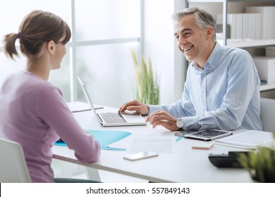 Confident advisor meeting with a customer in his office, he is explaining a contract document and policy to the woman sitting at his desk