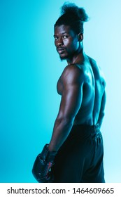 confident african american boxer with muscular torso looking at camera on blue background