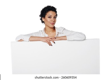 Confident african american business woman standing behind leaning at blank white banner, looking down at it, over white background