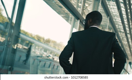 Confident african american businessman walking along big office windows outdoors. Modern building. Back view. Shot from back. Close up
