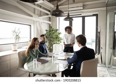 Confident African American businesswoman leading briefing, explaining strategy, training diverse staff sitting at table in boardroom, group negotiations, business partners sharing startup ideas
