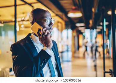 Confident african american entrepreneur dressed in formal wear calling on smartphone and discussing business project.Experienced dark skinned proud ceo in black suit talking on telephone device