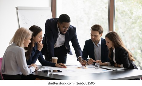 Confident african American male boss work cooperate with diverse team at office briefing, focused biracial businessman head meeting, collaborate discuss business ideas with colleagues at meeting