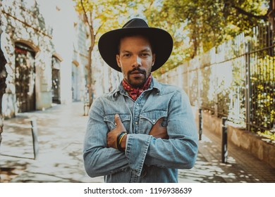 Confident African American male hipster wearing black hat and jeans shirt. Street wear fashion black man . Lifestile concept