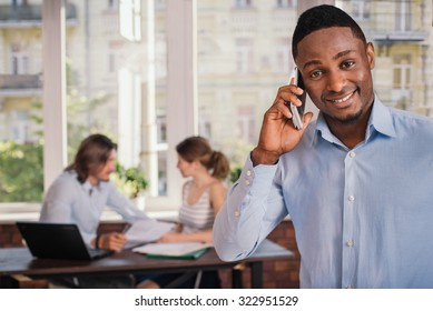 Confident african american man in formal wear waiting for job interview and talking on mobile phone