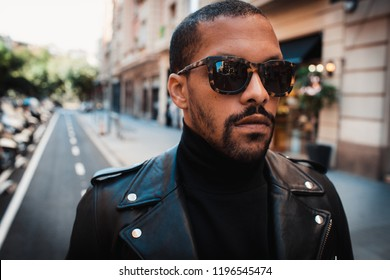 Confident african american man wearing on sunglasses and black leather jacket outdoor. Street wear fashion black man. Closeup