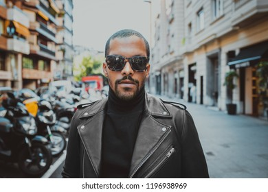 Confident african american man wearing on sunglasses and black leather jacket outdoor. Street wear fashion black man.