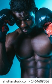 confident african american sportsman in boxing gloves looking at camera on blue background