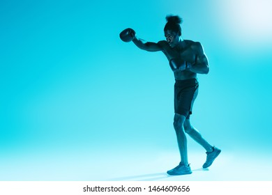 confident african american sportsman in boxing gloves training on blue background