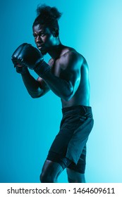 confident african american sportsman with muscular torso boxing on blue background