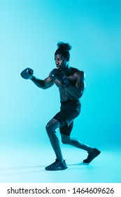 confident african american sportsman in shorts and sneakers boxing on blue background