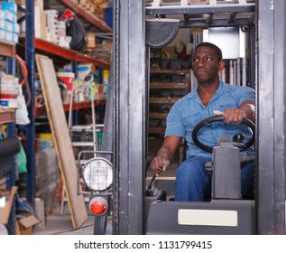Confident African American worker driving forklift in building materials shop