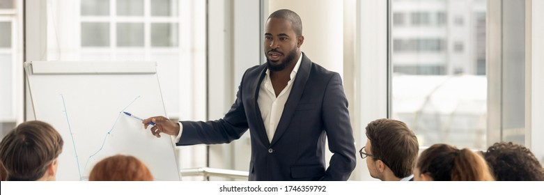 Confident African business coach gives presentation on flip chart, consults clients, teach employees, explain corporate strategy at seminar concept. Horizontal photo banner for website header design