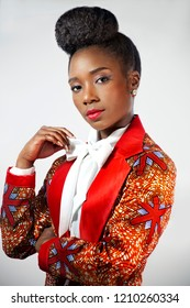Confident African business woman  wearing an African print suit and sophisticated hair style with her hand folded under her arm looking ahead
