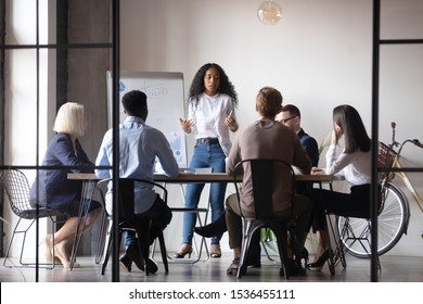 Confident african businesswoman presenter coach give corporate whiteboard presentation training multiracial people group explain project at team briefing staff conference, business education concept