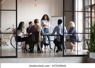 Confident african female trainer giving educational workshop to diverse team at office. Focused mixed race speaker standing near whiteboard, discussing project presentation with motivated coworkers.