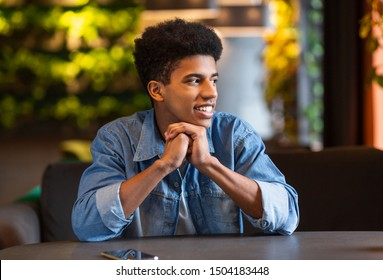 Confident african teen guy spending time alone at cafe, leaning on elbows and looking aside, copy space