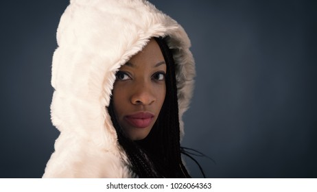 Confident African young woman close up studio portrait with braids and hood against dark background.