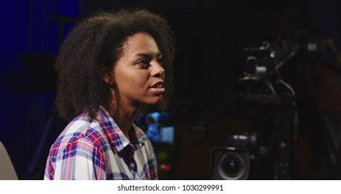 Confident African-American woman in casual shirt sitting in spotlight in telecasting studio and talking while presenting online show.