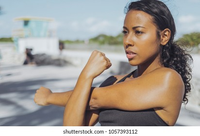 Confident African-American woman in sportswear training on waterfront in sunlight warming up hands and looking forward.
