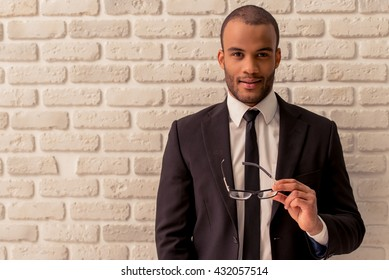 Confident Afro American businessman in classic suit is keeping eyeglasses, looking at camera and smiling, against white brick wall