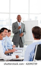 Confident Afro-American businessman discussing with his team in a presentation