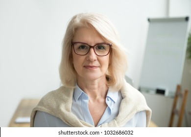 Confident aged businesswoman wearing glasses looking at camera, skilled experienced senior female professional, mature lady teacher coach posing in office alone, older woman boss head shot portrait