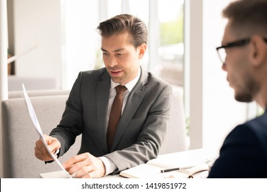 Confident agent in formalwear pointing at one of contract terms while explaining it to client, applicant or colleague at meeting