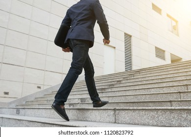 Confident ambitious businessman walking up the stairs